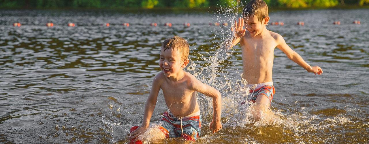 Zwei kleine Jungen spielen in einem See