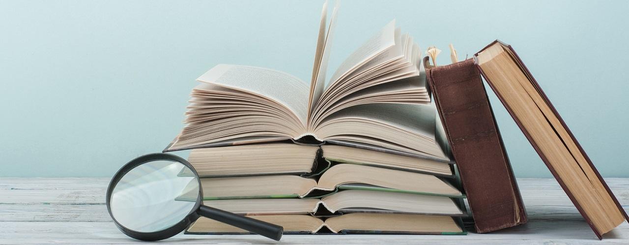 Gestapelte Bücher und eine Lupe