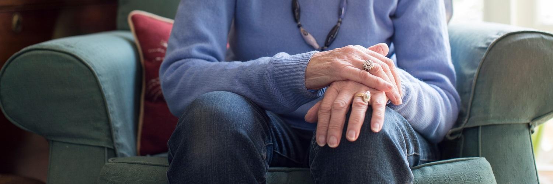 Seniorin mit zitternden Händen auf dem Sofa
