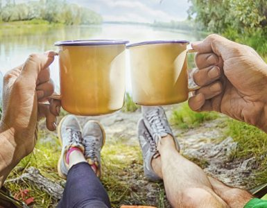 Paar genießt den Blick aus dem Zelt auf einen Fluss