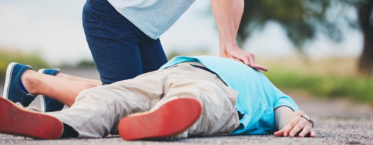 Ersthelfer versorgt einen am Boden liegenden Patienten mit Herzinfarkt