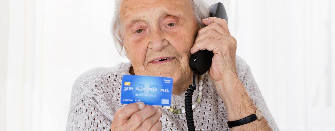 Seniorin am Telefon Kreditkrarte in der Hand
