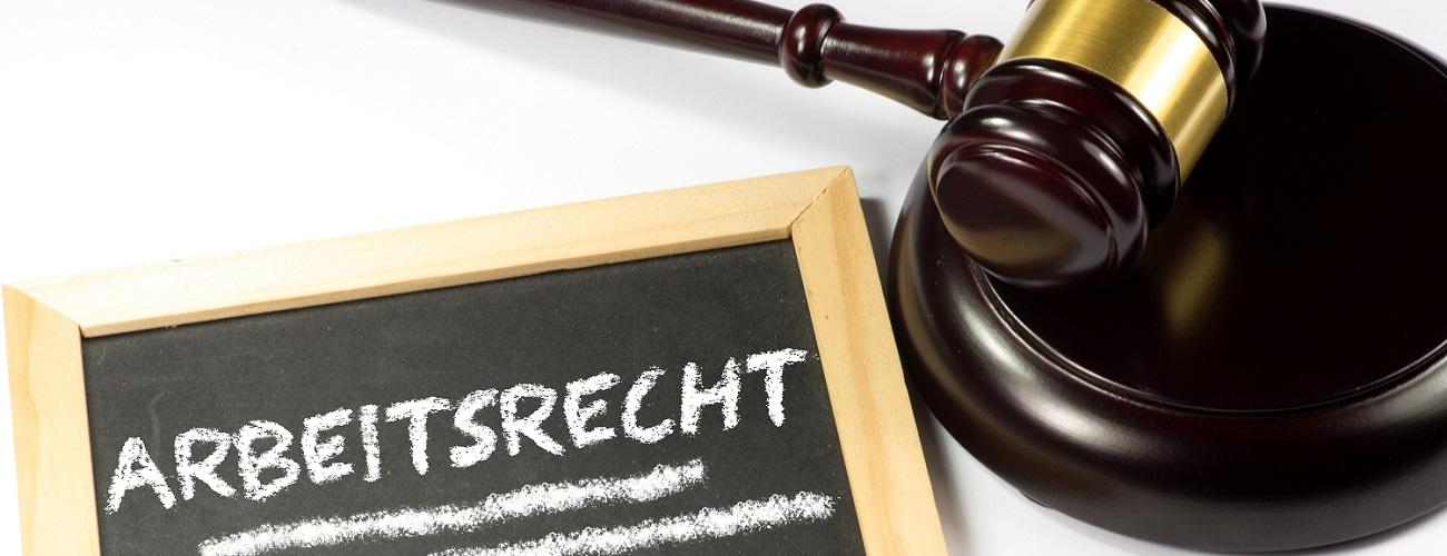 Gerichtshammer neben einer Tafel zum Arbeitsrecht