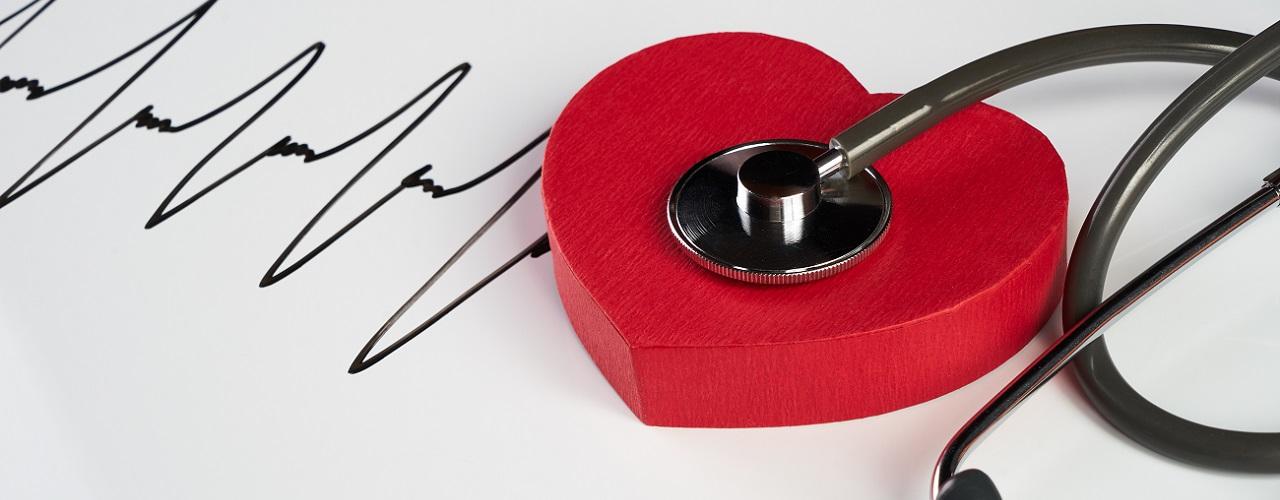 Stethoskop hört ein rotes Symbolherz ab um einen stillen Herzinfarkt zu erkennen
