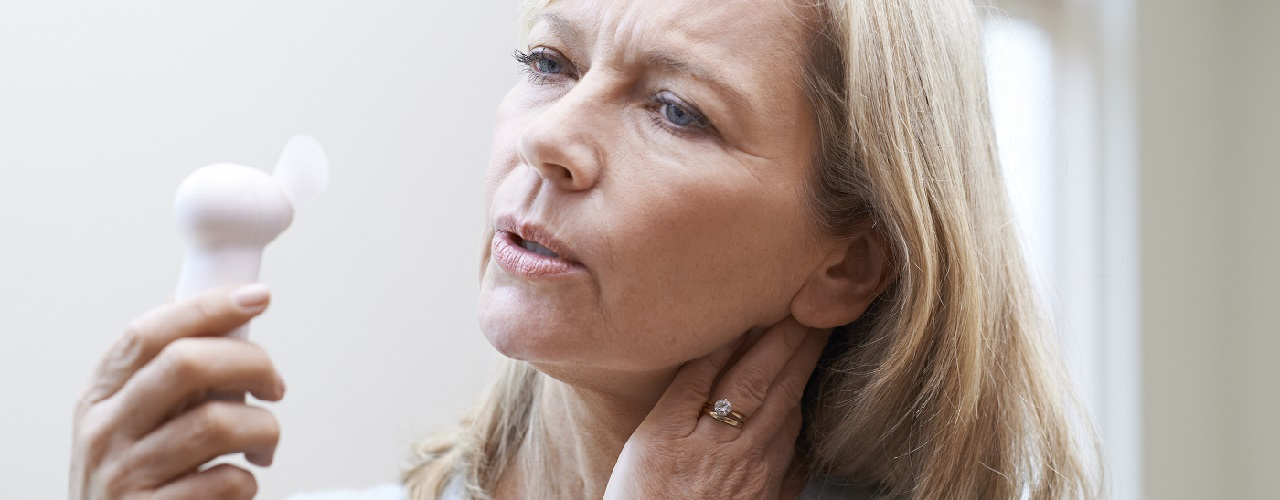Ältere Frau mit Ventilator kühlt ihr Gesicht