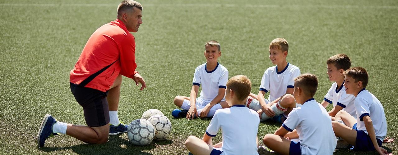 Fußballtrainer mit Kindern auf dem Trainingsplatz