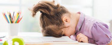 Kleines Mädchen legt Kopf auf Tischplatte