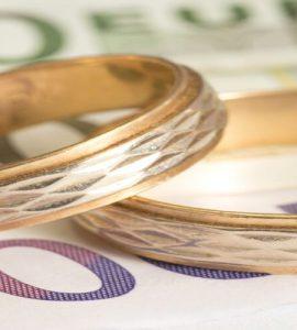 Eheringe liegen auf Geldschein