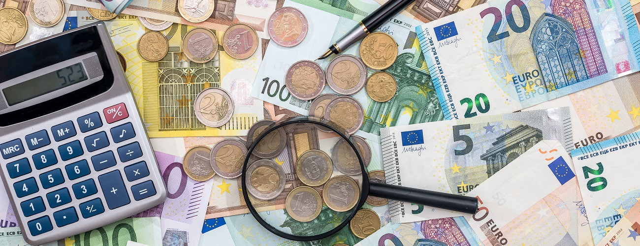 Geldscheine mit Lupe und Taschenrechner