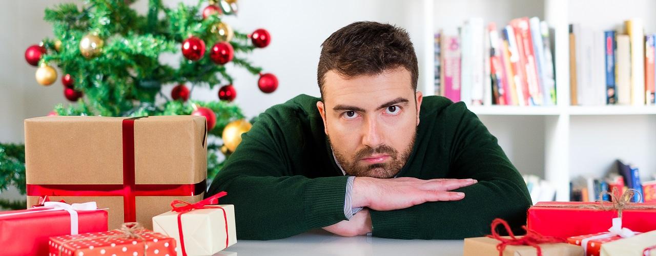 Mann sitzt zwischen Geschenken und hat keine Lust auf Weihnachten