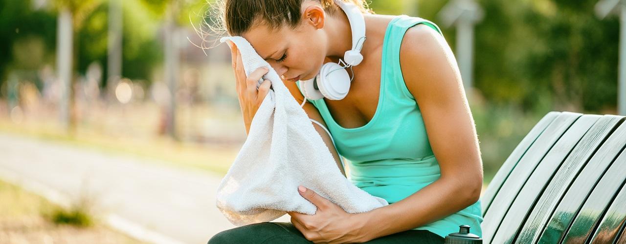 Ausgelaugte Sportlerin trocknet sich mit Handtuch ab