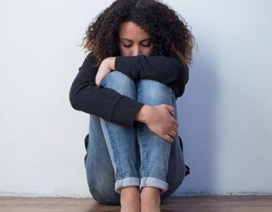 Trauriges schwarzes Mädchen sitzt auf dem Boden