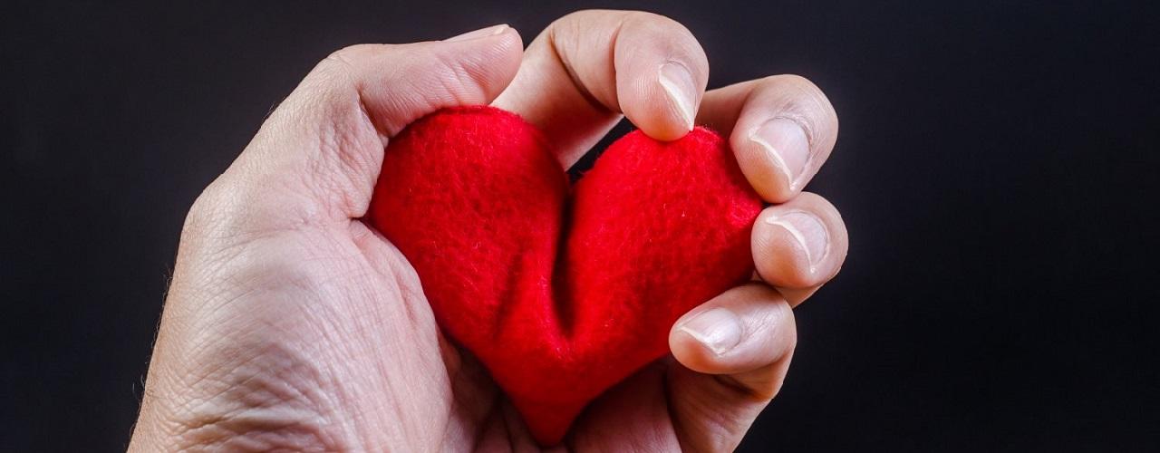 Eine menschliche Hand erdrückt ein Plastikherz.