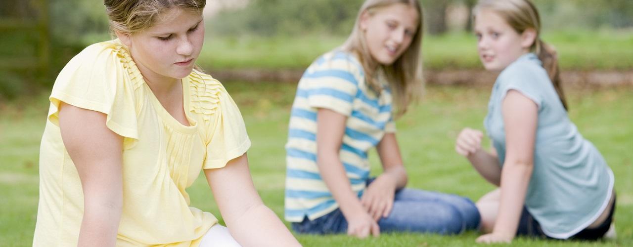 Mädchen sitzt abseits zweier Kinder