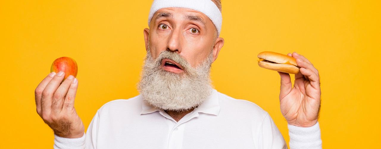 Sportlicher, älterer Mann mit Burger und Gemüse in der Hand