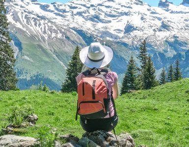 Frau sitzt auf Stein in den Bergen