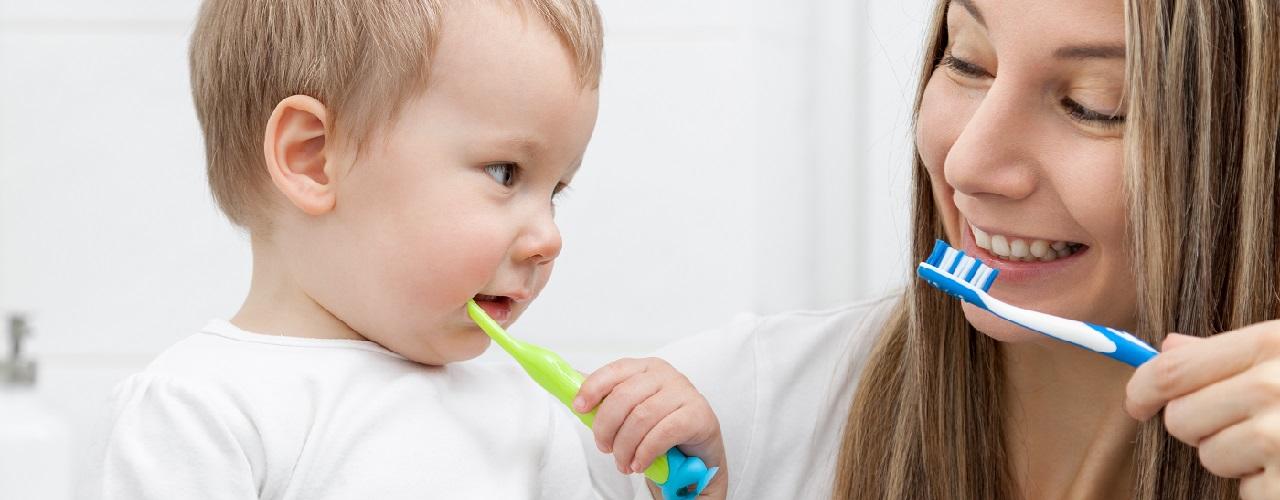 Kleiner Junge lernt mit seiner Mama das Zähneputzen