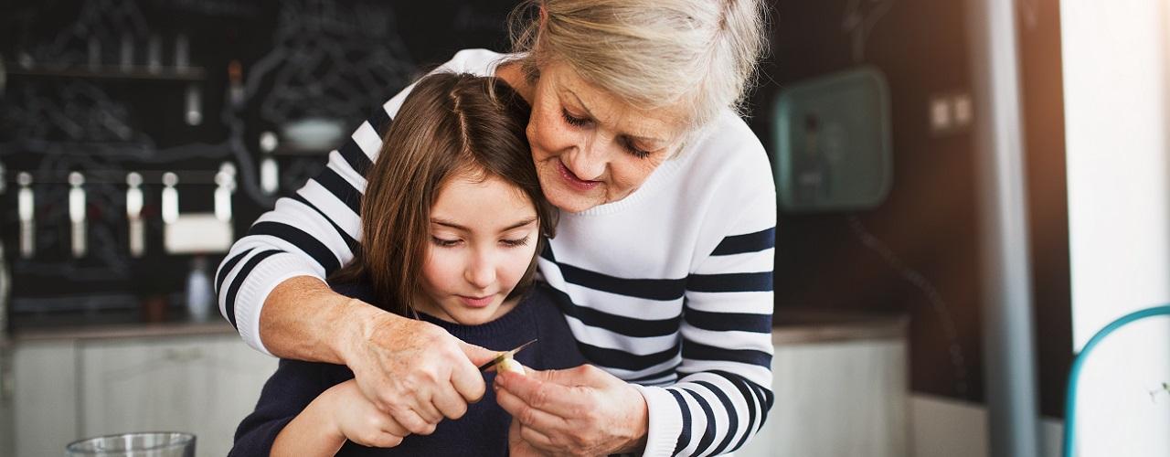 Leihoma steht mit einem Kind in der Küche beim Backen