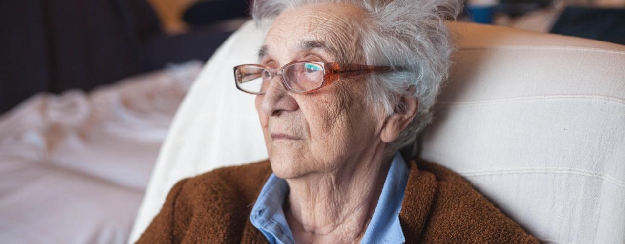 Eine ältere Dame im Krankenbett blickt in die Ferne und wirkt aufgrund der Demenz abwesend
