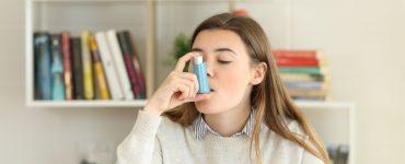 Frau inhaliert Asthmaspray