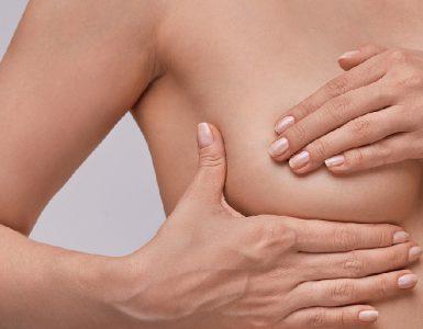 Frau tastet ihre Brust ab