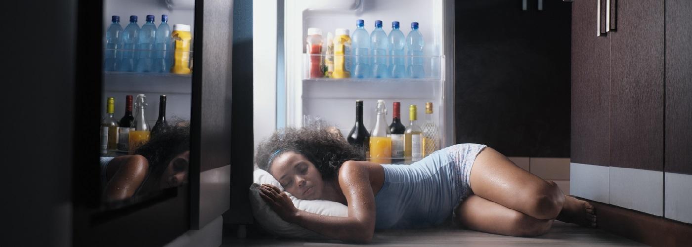 Eine junge Frau liegt schlafend vor einem offenen Kühlschrank um sich in heißen Nächten abzukühlen
