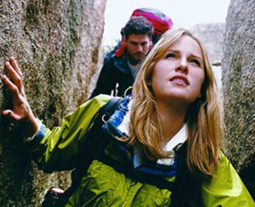 IDEAL Dread-Disease-Versicherung: Frau und Mann wandern zwischen Felsen