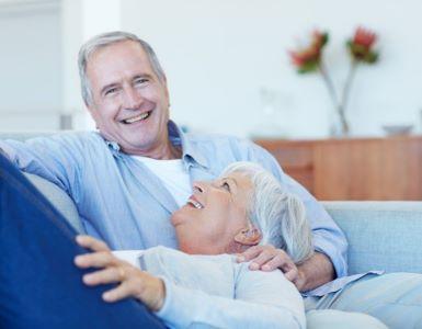IDEAL Unfallversicherung: Frau und Mann lachend auf dem Sofa