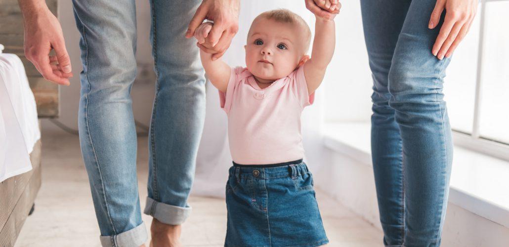 Kleinkind läuft mit Eltern an der Hand