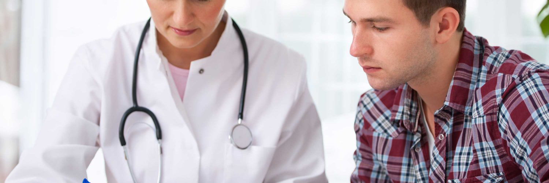 Junger Mann im Krebsvorsorge - Gespräch mit seiner Ärztin