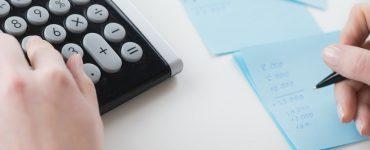 Hände mit Taschenrechne, Papier und Stift, Vorteile und Nachteile, Bilanz berechnen