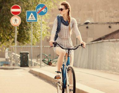 Fahradfahrerin im Verkehr, Straßenschilder zu beachten