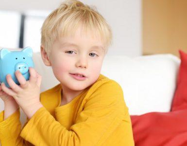 Kind mit Sparschwein in der Hand