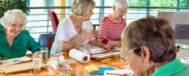 Ältere Damen sitzen am Tisch und basteln